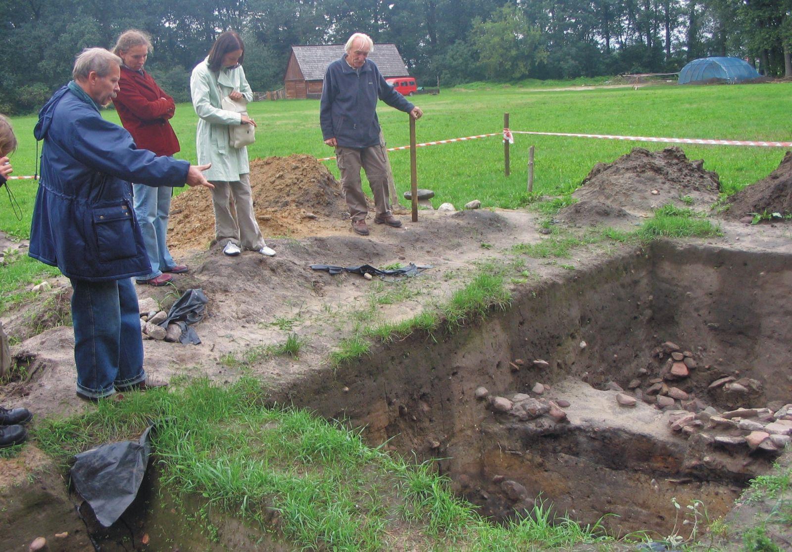 Czterech pracowników stoi nad wykopem archeologicznym w Grodzie w Grzybowie