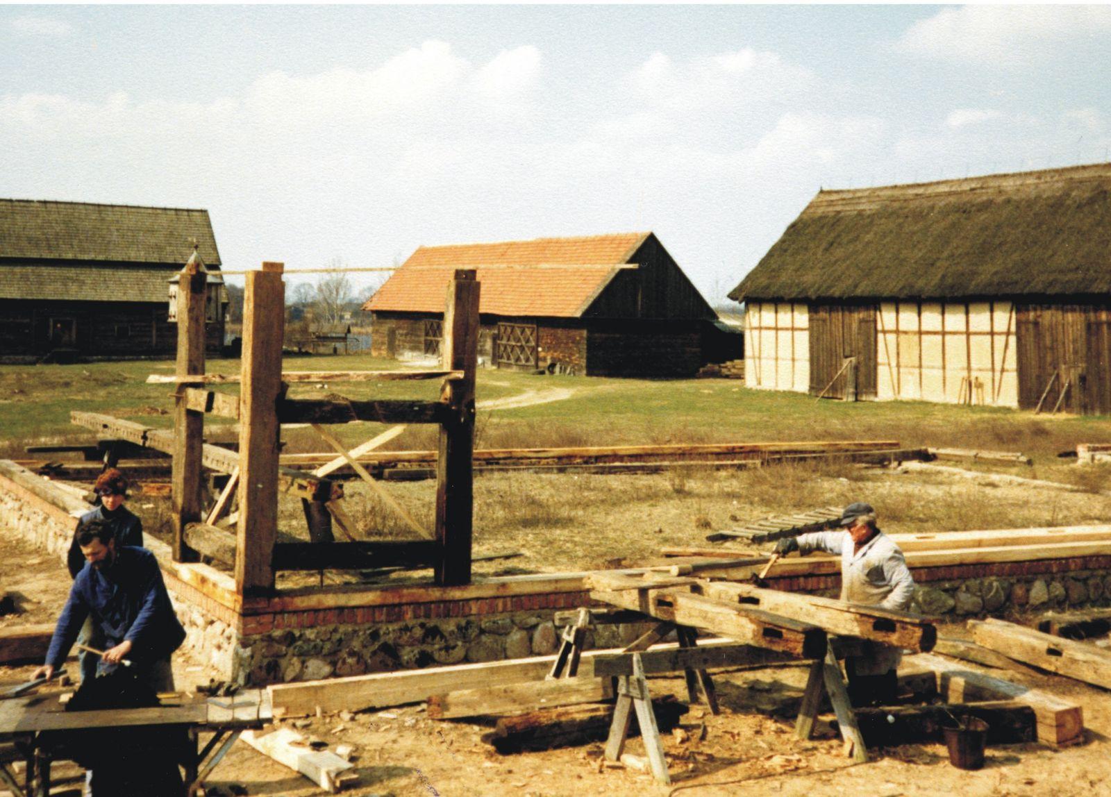 Trzech praconików muzeum podczas budowy stodoły. Widoczne fundamenty i drewniane pale.